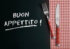 Bestick på den rutiga torkduken på Buon Appettito Royaltyfri Fotografi
