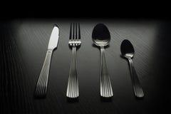 Bestick på en svart tabell Fotografering för Bildbyråer