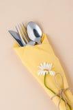 Bestick som slås in i en gul servett på en ljus persikabakgrund Royaltyfri Fotografi