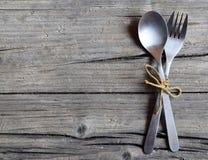 Bestickuppsättning: gaffel och sked på den lantliga trätabellen Bestick på gammal träbakgrund Kan användas som bakgrundsmenyn för Royaltyfri Fotografi