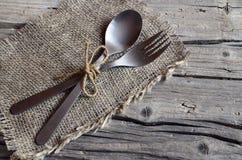 Bestickuppsättning: gaffel och sked på den lantliga trätabellen Bestick på gammal träbakgrund Kan användas som bakgrundsmenyn för Arkivfoton