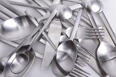 Bestickuppsättning med gaffeln, kniven och skeden på vit Arkivfoton