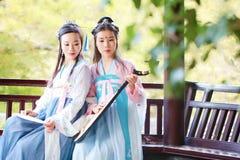 Bestie étroit d'amies dans la guitare antique traditionnelle chinoise de luth de pipa de jeu de costume Image stock