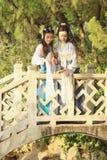 Bestie próximo das amigas no jogo antigo tradicional chinês do traje em um jardim Imagens de Stock Royalty Free