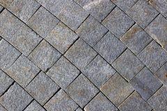 Bestrating van grijze granietstraatstenen die wordt gemaakt Stock Foto's