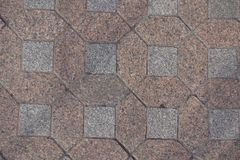Bestrating van roze en grijze niet gepolijste granietblokken dat wordt gemaakt stock foto's