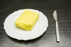 Bestreichen Sie auf einer weißen Platte und einem Messer auf dem Tisch mit Butter Stockbilder