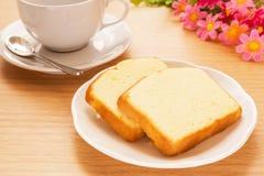 Bestreichen Sie den Kuchen mit Butter, der auf Platte und Kaffeetasse, gefiltertes Bild geschnitten wird Stockbild