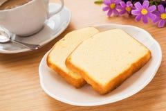 Bestreichen Sie den Kuchen mit Butter, der auf Platte und Kaffeetasse geschnitten wird Lizenzfreie Stockbilder
