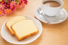 Bestreichen Sie den Kuchen mit Butter, der auf Platte und Kaffeetasse geschnitten wird Stockfoto