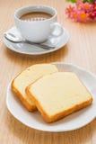 Bestreichen Sie den Kuchen mit Butter, der auf Platte und Kaffeetasse geschnitten wird Lizenzfreies Stockbild