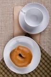 Bestreichen Sie ein rundes Brötchen - Bagel mit Butter Lizenzfreie Stockfotografie