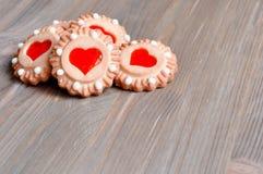 Bestreichen Sie Keksplätzchen mit rotem Gelee in Form von Herzen auf dem braunen Holztisch mit Butter Stockfotografie