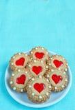 Bestreichen Sie Keksplätzchen mit rotem Gelee in Form von Herzen auf dem weißen Limpet mit Butter Lizenzfreies Stockbild