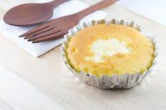 Bestreichen Sie Kuchen in der Folienschale auf hölzernem Schreibtisch mit Butter Stockbild