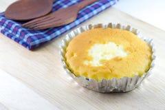 Bestreichen Sie Kuchen in der Folienschale auf hölzernem Schreibtisch mit Butter Stockfotografie