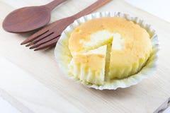 Bestreichen Sie Kuchen in der Folienschale auf hölzernem Schreibtisch mit Butter Stockfoto