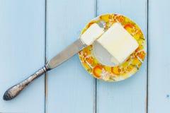 Bestreichen Sie mit Buttermesser auf einem Weinleseholzhintergrund mit Butter Stockfotos