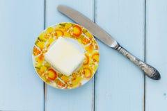 Bestreichen Sie mit Buttermesser auf einem Weinleseholzhintergrund mit Butter Stockbild
