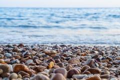 Bestreuen Sie Schärfentiefe und blauen Seehintergrund mit Kies Stockbilder
