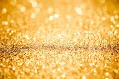 Bestrooi gouden glanzend stof op een zwarte achtergrond royalty-vrije stock afbeeldingen
