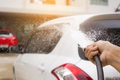 Bestrooi met water om de auto met de hand te wassen stock foto