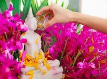 Bestrooi water op een beeld van Boedha, een gebaar van verering tijdens het jaarlijkse Songkran-festival stock fotografie
