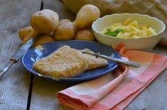 Bestruken ost med självodlade skalade potatisar på träbakgrund Royaltyfri Fotografi