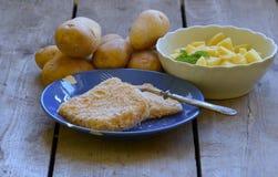 Bestruken ost med självodlade skalade potatisar på träbakgrund Royaltyfria Bilder