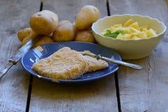 Bestruken ost med självodlade skalade potatisar på träbakgrund Arkivfoto