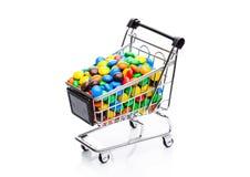 Bestrukna söta godisar för runda i shoppingvagn Arkivbilder