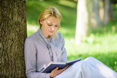 Bestseller top list. Books every girl should read. Relax leisure an hobby concept. Best self help books for women. Girl. Concentrated sit park lean tree trunk stock photos