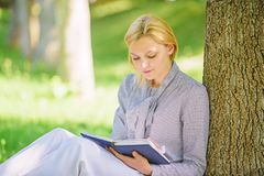 Bestseller top list. Books every girl should read. Relax leisure an hobby concept. Best self help books for women. Girl. Concentrated sit park lean tree trunk royalty free stock photos