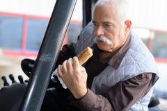 Bestuurder die brood eten terwijl het drijven van klassieke tractor Stock Foto