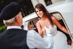 Bestuurder die bruid helpen om uit de auto te krijgen Royalty-vrije Stock Fotografie