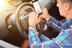 Bestuurder die een telefoon in een auto opgeheven mening met behulp van stock fotografie