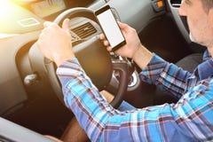 Bestuurder die een voertuig drijven die een gevaarlijk opgeheven telefoon raadplegen stock foto's