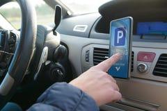 Bestuurder die smartphone app gebruiken om voor parkeren te betalen royalty-vrije stock foto