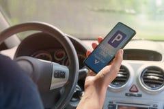 Bestuurder die smartphone app gebruiken om voor parkeren te betalen royalty-vrije stock fotografie