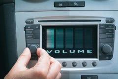 Bestuurder het aanpassen volume in het auto audiosysteem stock foto's