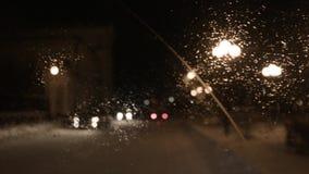 Bestuurder het drijven op een regenachtige nacht in een stad, mening van binnenuit lengte Mening van het windscherm van de auto i stock footage