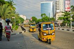 Bestuurders van gele tuk tuks vouw hun handel rond de havenstad stock afbeelding