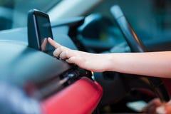 Bestuurdershand die een adres in het navigatiesysteem of radiolied in auto ingaan royalty-vrije stock afbeeldingen