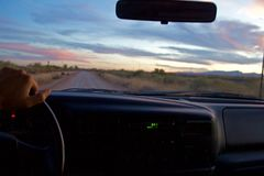 Bestuurdersstandpunt van een aandrijving op een landweg na zonsondergang, één hand op het wiel stock foto