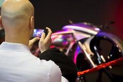Besucher, der ein Foto eines Motorrades auf Anzeige an Eurasien-motobike Ausstellung macht Stockbilder