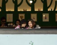 Besucher des Straßencafés mit Telefon Lizenzfreie Stockfotografie