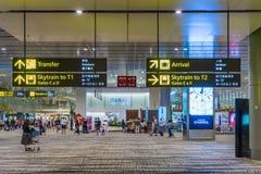 Besucher gehen um Abfahrt Hall in Changi-Flughafen Singapur Lizenzfreie Stockbilder