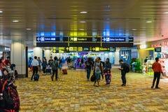 Besucher gehen um Abfahrt Hall in Changi-Flughafen Singapur Stockfotografie
