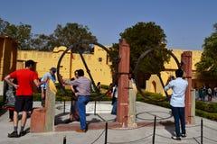 Besucher mit Fremdenführer am ringförmigen Instrument am astronomischen Observatorium Jaipur, Rajasthan, Indien Lizenzfreies Stockfoto