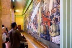 Besucher, welche die Wandgemälde durch Diego Rivera bei Palacio de Bellas Artes in Mexiko City bewundern stockfotos